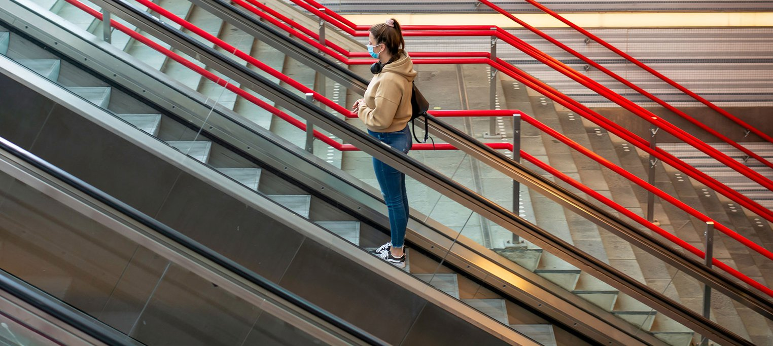 Young woman alone on escalators with PPE mask