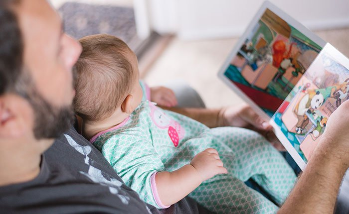 Father reads book to baby