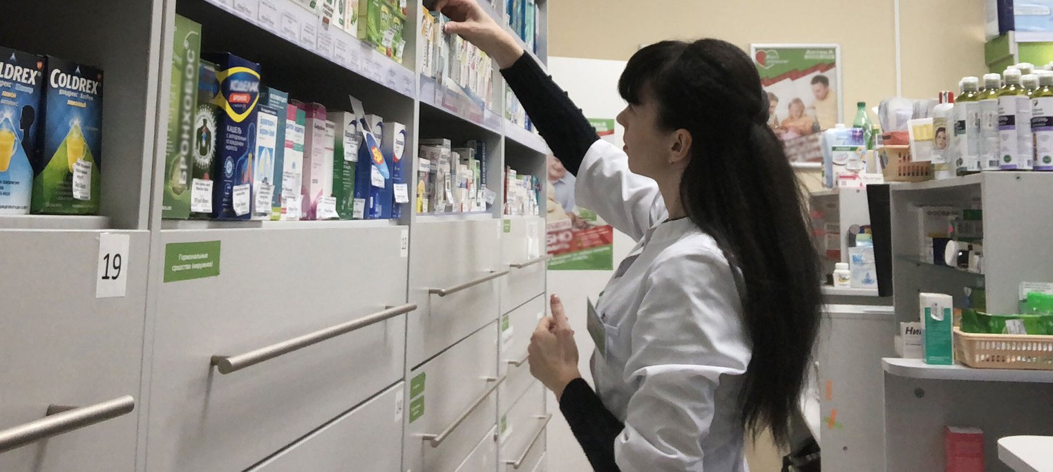 Pharmacist browsing medication shelves