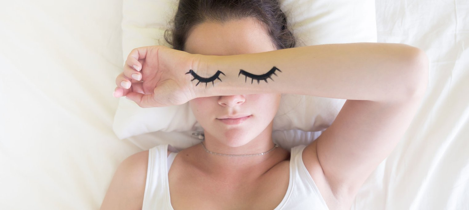 Woman in bed with arm over face, closed eyes are painted on arm.