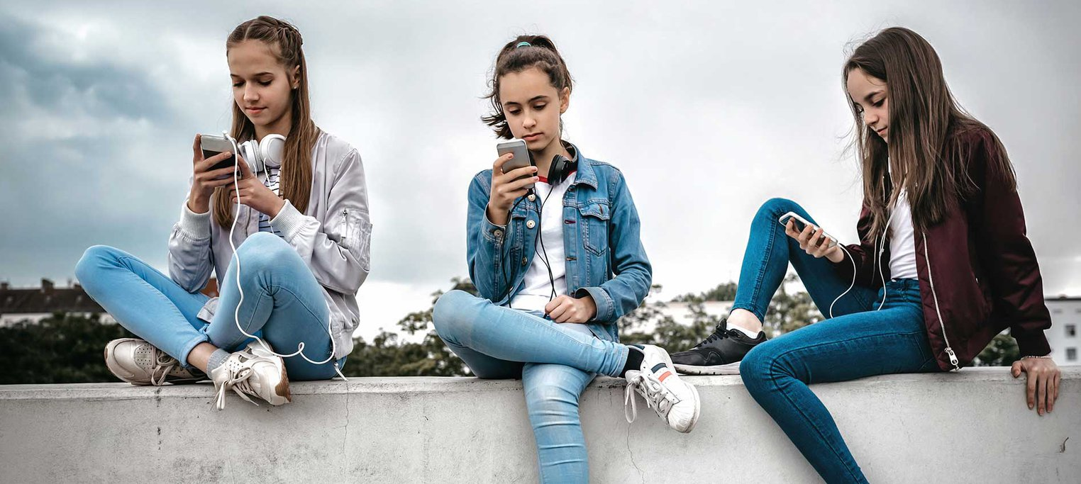 3 young women looking at their phones